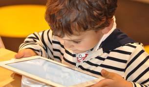 Un niño juega con una tablet.