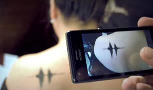 Una persona escucha, con ayuda de un móvil, un tatuaje sonoro.