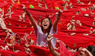 Una joven se levanta por encima de la multitud de pañuelos rojos, en la plaza del Castillo tras el lanzamiento del chupinazo en Sanfermines.