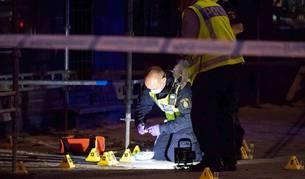 foto de Agentes de la policía forense investigan la escena después de un tiroteo producido en Malmo fuera de un cibercafé.