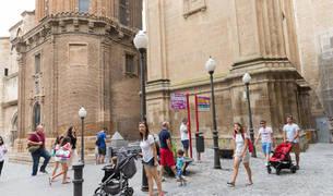DISFRUTANDO DE LA CALLE. Varios turistas pasean por las inmediaciones de la Catedral y la plaza Vieja mientras observan la fachada del Ayuntamiento.