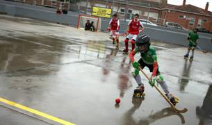 Jóvenes disputan un partido de hockey un día de lluvia en el patinódromo municipal de Tudela.