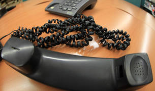 Un teléfono fijo, descolgado sobre una mesa.