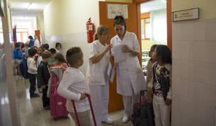 Dos trabajadoras de Ausolan, la principal empresa prestataria del servicio, preparan la entrada al comedor en el Colegio Público Iturrama.