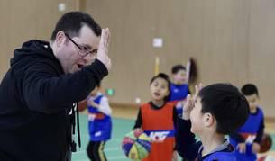 El entrenador Jesús Casimiro choca la mano con uno de los niños a los que enseña baloncesto.