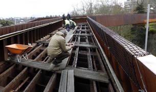El perito y dos de sus ayudantes agachados este miércoles mientras fotografiaban el esqueleto de la pasarela. Al fondo, los técnicos municipales.