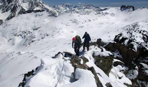 Dos alpinistas, encordados en una arista nevada durante una actividad.