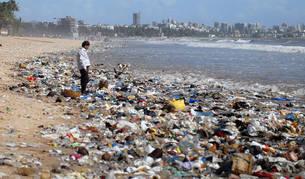 Foto de un hombre observando una montaña de residuos plásticos a orillas del Mar Arábigo en Bombay, India.