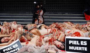 Activistas protestan contra la industria peletera simulando ser animales desollados