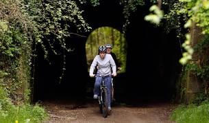 Foto de dos cicloturistas atravesando uno de los túneles de la Vía Verde del Plazaola.