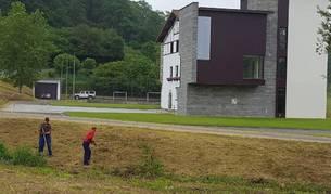 Dos operarios adecúan una franja de terreno, próxima a la actual casa consistorial de Larraun.