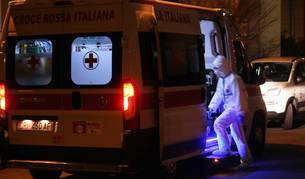 Un sanitario con máscara y protección entra en una ambulancia a puertas del Hospital Sacco de Milán.