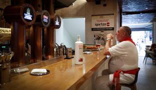 Un hombre toma un vino este martes, 14 de julio, en un bar de Pamplona vestido de blanco y rojo.