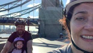 Paula Bellostas, su marido Geoff y su hija Lucía, en bici por el London Bridge, cerca de su casa.