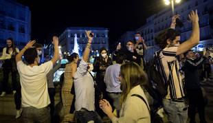 Jóvenes en la Puerta del Sol de Madrid esta madrugada.