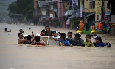Un grupo de personas intenta escapar del agua en un suburbio de Manila
