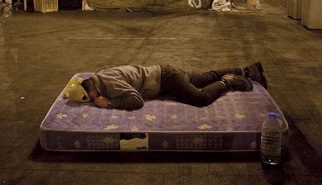 Un mendigo durmiendo en un colchón en la calle de Madrid