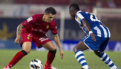 El defensa del RCD Mallorca, Ximo Navarro (i), intenta superar al centrocampista ghanés del RCD Español, Wakaso Mubarak