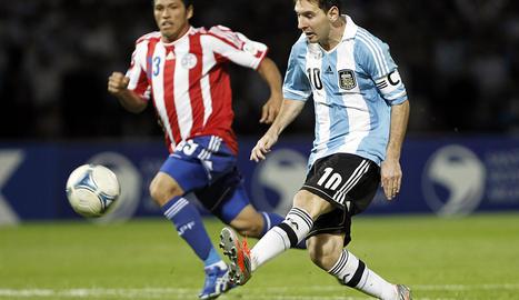 Lionel Messi (dcha.) de Argentina juega la bola ante el defensa Richard Ortíz (izda.) de Paraguay.