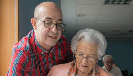 Miguel Lasaosa Zazo, voluntario de Cruz Roja, da cursos a mayores sobre el uso de teléfonos inteligentes. En la imagen, con una alumna.