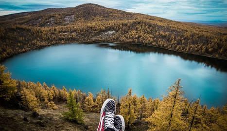 foto de un viajero descansando en la naturaleza viendo un lago