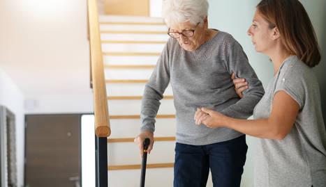 Foto persona mayor bajando unas escaleras con ayuda de una joven