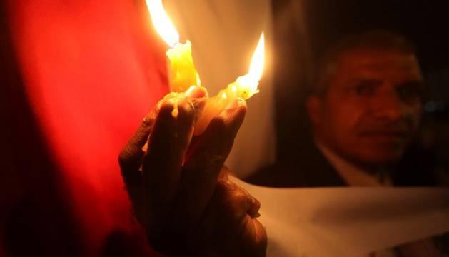 Un ciudadano egipcio sostiene unas velas en la concentración de la plaza Tahrir de El Cairo el 31 de diciembre de 2011