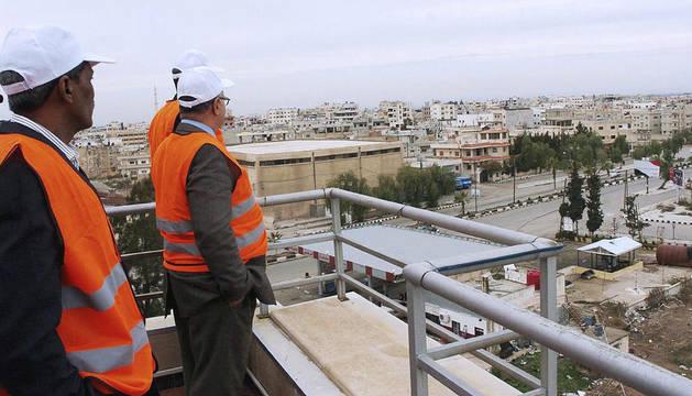 Observadores de la Liga Árabe observando desde la terraza de un edificio la ciudad de Daraa
