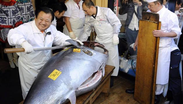 El presidente de la cadena de Sushi-Zanmai, Kiyoshi Kimura, corta por la mitad un atún de aleta azul del Pacífico