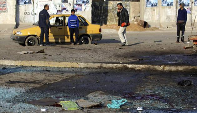 Iraquíes en el escenario de un atentado con bomba en Ciudad Sadr, al este de Bagdad este jueves.