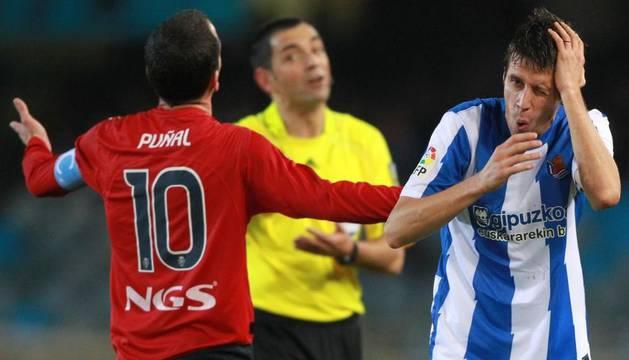 El centrocampista de la Real Sociedad, Mikel Aranburu (derecha) tras recibir un golpe del centrocampista de Osasuna Patxi Puñal en presencia del colegiado Teixeira Vitienes