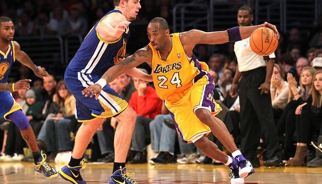 El escolta de los Lakers, Kobe Bryant (dcha.) trata de zafarse de la defensa del jugador de Golden State Warriors, David Lee