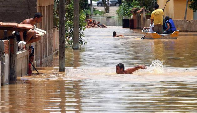 Un grupo de personas se desplaza por una calle inundadas de la localidad de Campos Dos Goytacazes (Brasil)