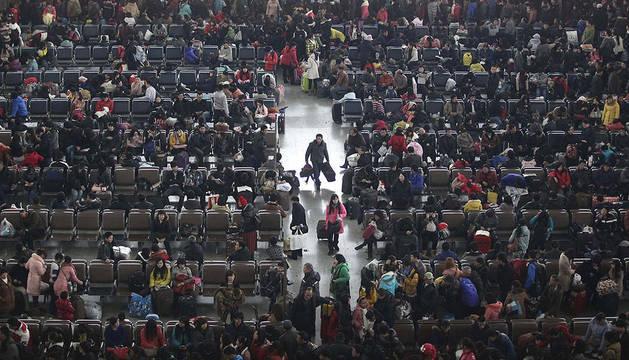Un policía mantiene el orden en frente de filas de personas que esperan para comprar billetes de tren en la estación Kunning