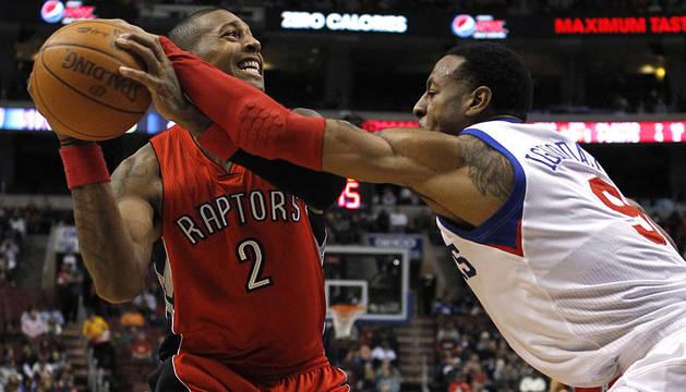 El jugador de Toronto Raptors, James Johnson (izda.) intenta buscar el pase ante la defensa del jugador de Filadelfia Sixers, Andre Iguodala