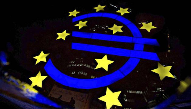 El logo del euro del Banco Central Europeo queda reflejado en un charco en Fráncfort