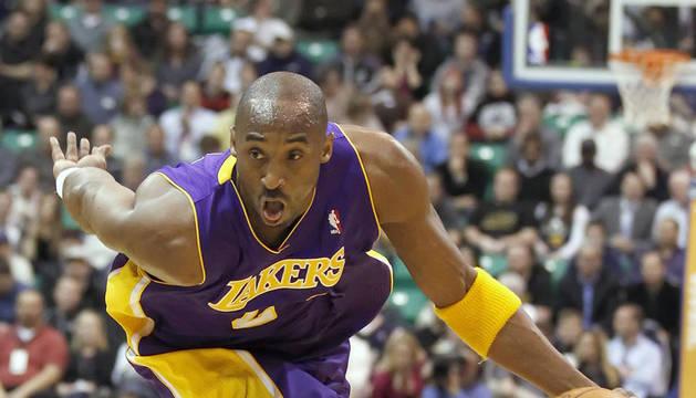 El jugador de los Lakers Kobe Bryant maneja el balón durante un partido