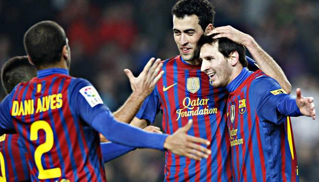 Messi celebra su tanto con Alves y Busquets.