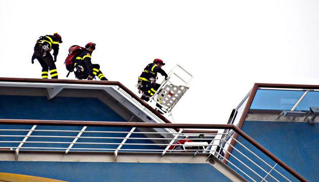 Tres bomberos trabajan a bordo del buque crucero Costa Concordia en las tareas de rescate de supervivientes