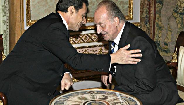 El rey Juan Carlos charla con el presidente francés, Nicolas Sarkozy, durante el encuentro mantenido en el Palacio Real antes de imponerle el Collar de la Orden del Toisón de Oro