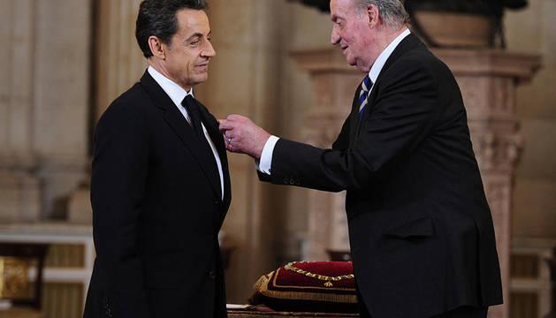 Don Juan Carlos coloca en su chaqueta el toisón de Oro a Sarkozy.