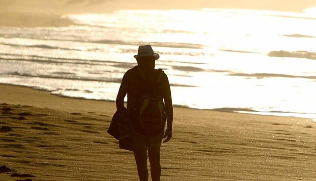 Un hombre pasea por la playa de la Zurriola de San Sebastián al atardecer