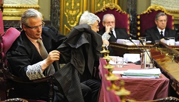 El juez Baltasar Garzón (i), junto a su abogado Francisco Baena Bocanegra (2i), durante el juicio que se sigue contra él en el Tribunal Supremo por ordenar grabar las conversaciones en prisión entre los imputados del