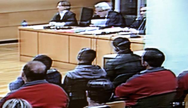 Imagen tomada de un monitor de televisión de los tres acusados durante el inicio del juicio