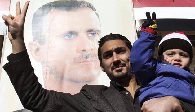 Un hombre sostiene en brazos a su hijo durante una manifestación de apoyo al régimen de Bachar El Asad