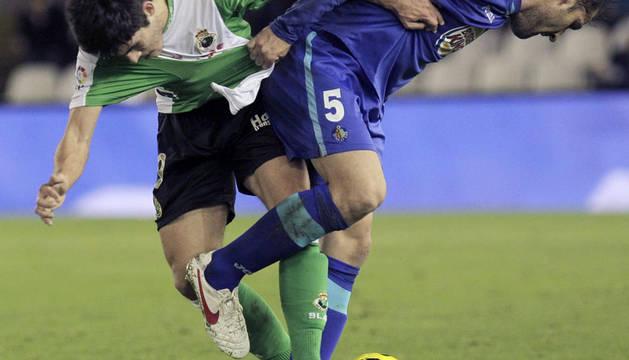 El centrocampista del Racing de Santander Jairo Samperio (i) disputa el balón con el defensa del Getafe CF Albert Lopo durante el partido