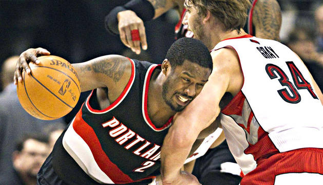 El jugador de los Blazer, Wesley Matthews (izda.) trata de marcharse del jugador de Toronto Raptors, Aaron Gray (dcha.)