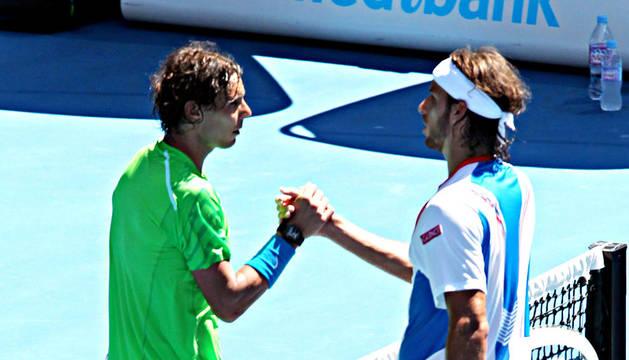 El tenista español Rafael Nadal (izda.) estrecha la mano de su compatriota Feliciano López (dcha.) tras el choque de octavos de final del Open de Australia 2012