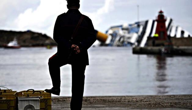 Un policía observa desde el puerto de Isola el estado del crucero Costa Concordia naufragado ante las cosas italianas