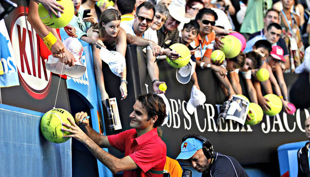 El tenista suizo Roger Federer firma autógrafos tras imponerse al argentino Juan Martín del Potro en los cuartos de final del Abierto de Australia en el Rod Laver Arena en Melbourne (Australia)